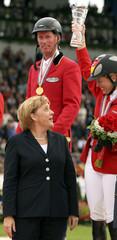 German Chancellor Angela Merkel speaks with German Individual Showjumping bronze medalist Meredith Michaels-Beerbaum (R) as gold medalist Jos Lansink of Belgium looks on at the World Equestrian Games in Aachen
