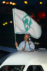 WERDER BREMEN'S COACH SCHAAF HOLDS A FLAG AND A VIDEO CAMERA LOOKING OUT OF A HATCH OF AN AIRPLANE ...