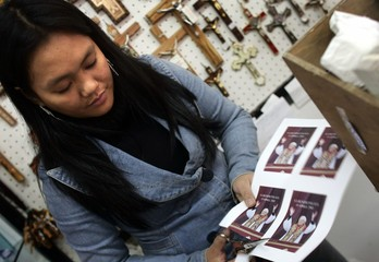 A shop owner cuts portraits of the new elected Pope Benedict XVI near the Vatican.