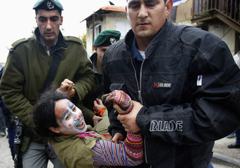 A demonstrator dressed as a clown is arrested by Israeli police during a sit-in demonstration in Jerusalem