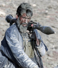 ANTI-TALIBAN AFGHAN FIGHTER HEADS TO FRONT IN THE TORA BORA MOUNTAINS.