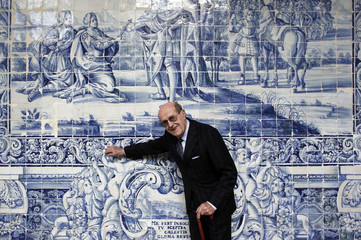 Portuguese movie director de Oliveira gestures in front of wall of tiles in Lisbon