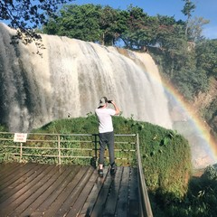 парень фотографирует на телефон водопад с радугой