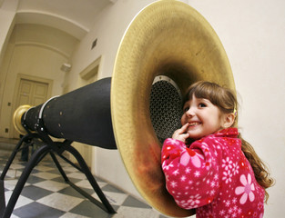 """A girl listens to a device at an interactive exhibition called the """"Orbis Pictus"""" in Prague"""