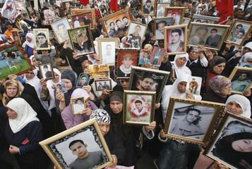 """Palestinian women hold pictures of jailed relatives during a protest marking """"Palestinian Prisoners Day"""" in Nablus"""