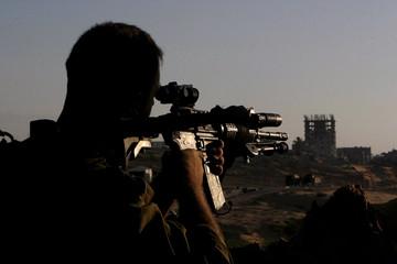 Israeli soldier aims rifle at surrounding area of Jewish Gaza Strip settlement of Netzarim.
