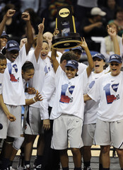 Connecticut Huskies players celebrate with the trophy after their defeat of the Louisville Cardinals in the NCAA women's Final Four Championship basketball game in St. Louis