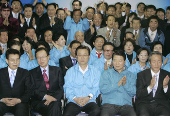 Ruling Grand National Party chairman Kang, GNP candidate Chung and other GNP members watch a television report in Seoul