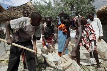 Maasai men and women work at the construction of a new room at Shompole