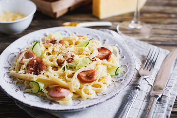 Italian food, vermicelli, spaghetti with fried sausages, cheese, cucumber, spices and white wine on a dark wooden background