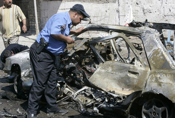 A police officer inspects a destroyed vehicle used in a car bomb attack which targeted pilgrims in Baghdad