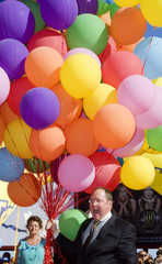 Lasseter, chief creative officer of Walt Disney and Pixar Animation Studios, holds balloons at Venice Film Festival