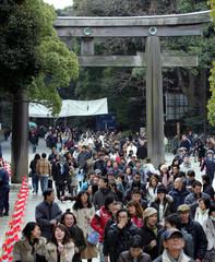 Japanese worshippers walk through wooden torii gate at Meiji Shrine in Tokyo