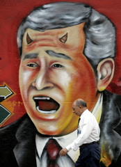 A Brazilian man walks past a mural depicting U.S. President George W. Bush with devil horns, in Rio ..