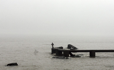 A man uses his fishing net during a foggy afternoon in a wharf on the coast of Montevideo
