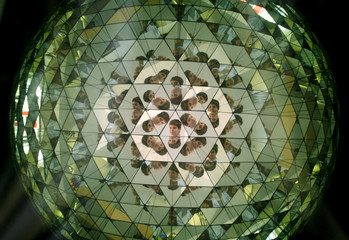 """A boy is seen in a kaleidoscope exhibit as he visits the interactive exhibition """"Orbis Pictus"""" in Prague"""