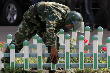 Chinese paramilitary policemen in riot gear cleans a fence surrounding a flower garden on a main street in the city of Urumqi in China's Xinjiang Autonomous Region