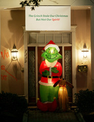 A Grinch blow-up doll stands under a sign in the Lakeview area of New Orleans
