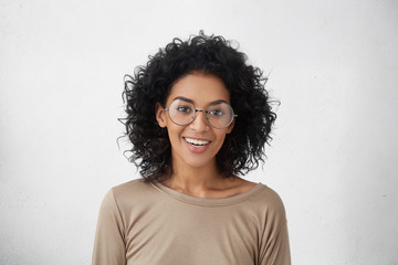 People and lifestyle. Emotions and feelings. Cute positive dark-skinned student girl in casual wear and stylish round eyeglasses smiling happily, feeling excited about first day at university