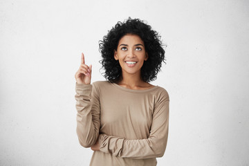 Waist up shot of joyful girl wearing beige long sleeve t-shirt looking up, pointing finger at copy space above her head. Black young woman indicating something on blank studio wall with hand Wall mural