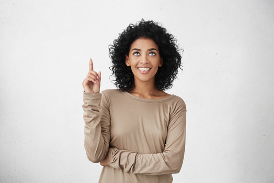 Waist up shot of joyful girl wearing beige long sleeve t-shirt looking up, pointing finger at copy space above her head. Black young woman indicating something on blank studio wall with hand