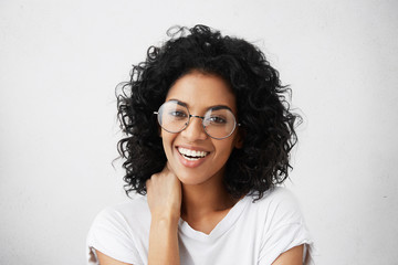 Positive human emotions. Portrait of beautiful and charming female student with Afro hairstyle, having shy look, laughing at camera, wearing stylish round eyeglasses, touching her neck with hand