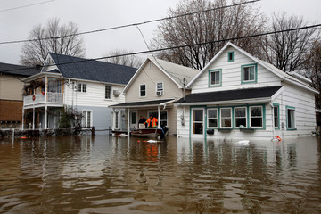 Men stand on the front porch of a home in a flooded residential area in Gatineau