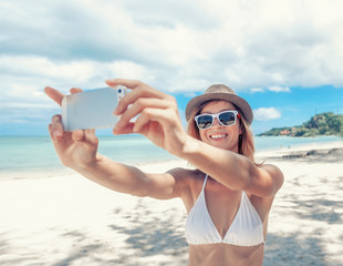 Happy pretty woman using mobile phone on the tropical beach, take a picture of trip