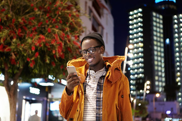 Handsome young dark-skinned hipster in hat, eyewear and winter coat messaging his girlfriend online on smart phone while waiting for her on street at night, looking at screen with joyful smile