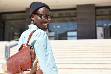Outdoor portrait of cheerful young African American male writer in trendy eyewear and hat hurrying to modern building for job interview with big magazine, having excited expression on his face
