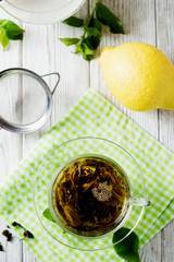 Drinks, green leaf tea with sugar, mint and lemon on a white rustic wooden background