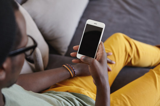 Unrecognizable stylish Afro American man wearing yellow jeans relaxing at home, lying on comfortable sofa, reading message on smart phone with black blank copy space screen for your information