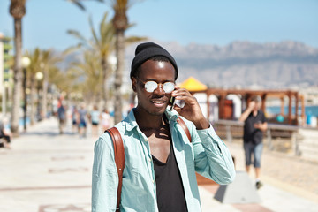 Close up picture of handsome confident young dark-skinned European male hipster wearing mirror lens shades and hat walking on streets of metropolis on sunny day and talking on generic mobile phone