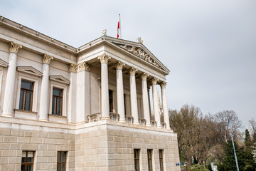 main entrance of Austrian parliament building in Greek style with statues of philosophers and white columns with famous Pallas Athena fountain and in Vienna