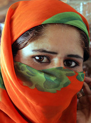A Kashmiri Muslim woman voter hides her face with a scarf during the second phase of municipal ...