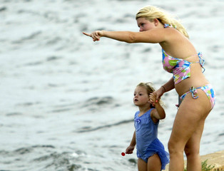 A woman and her daughter watch the waves on Pensacola Beach as Hurricane Dennis heads towards Florida.