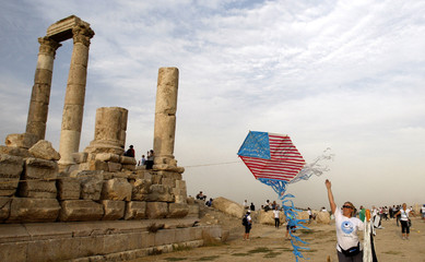 A member of the Follow the Women Foundation releases a kite depicting a U.S. flag during a tour at the Amman Citadel