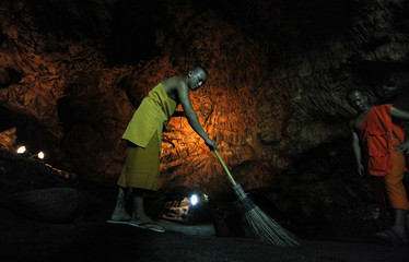 A Buddhist monk sweeps up bat guano in a cave near Wat Khao Cong Phran Temple in Ratchaburi province