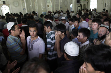 Ethnic Uighurs start to leave a mosque after Friday prayers in Urumqi