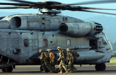 U.S marines drag a fellow soldier to a waiting Super Stallion during an anti-terrorist raid drill inside an airforce base in Pampanga province, north of Manila