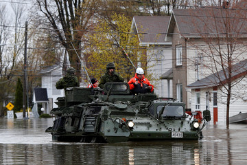 Canadian soldiers inspect a flooded residential area in Gatineau