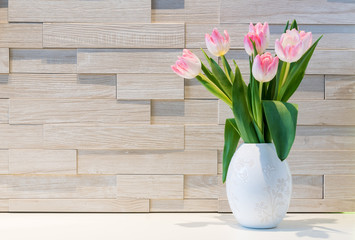 Beautiful bouquet of fresh tulips flowers against brick wall background