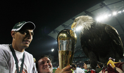 Benfica's Oscar Cardozo of Paraguay shows the trophy to the team's pet Victoria after winning the Portuguese League Cup final against Sporting in Faro