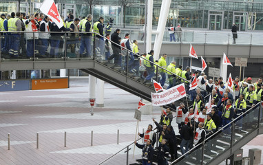 Airport employees walk through Munich's airport during a warning strike