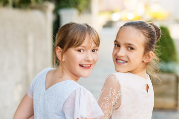Outdoor portrait of two sweet kid girls wearing party dresses