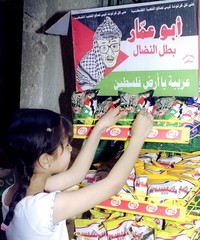 EGYPTIAN GIRL BUYS AN ABU AMMAR SNACK WITH CARTOON OF YASSER ARAFAT ONPACKAGING IN CAIRO.