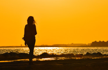 Young girl walking alone near seashore at sunset, silhouette.