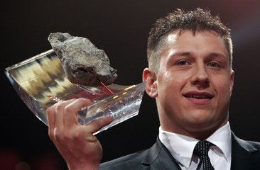 Swiss Alpine wrestler Abderhalden poses with his trophy after being awarded Swiss person of the year