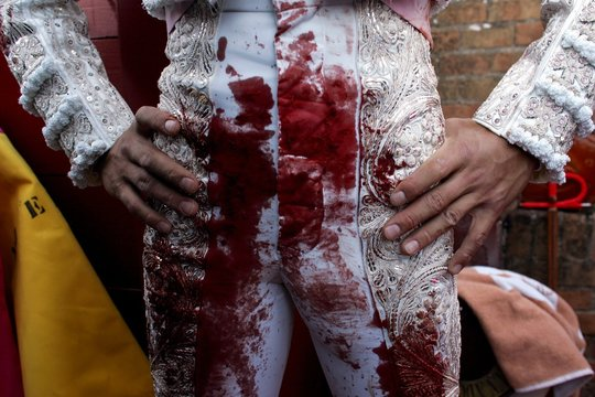 Spanish matador Cesar Jimenez stands in space between inner and outer barriers after killing a bull ...