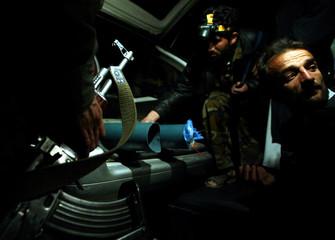 AFGHAN POLICEMEN DEFUSE IMPROVISED ROCKET LAUNCHERS IN KABUL.